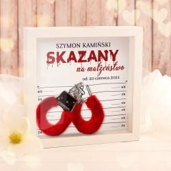 """Biała ramka z szybką. W środku są czerwone puchowe kajdanki. Ramka ma zabawny napis """"Skazany na małżeństwo"""""""