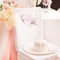 Pokrowiec na krzesło w białym kolorze. Udekorowany w kwiatową grafikę. Idealny dodatek na Wieczór Panieński.