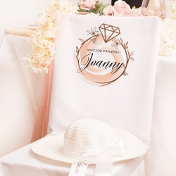 Pokrowiec biały na krzesło z wysokiej jakości materiału. Na nim widnieje miejsce na imię panny młodej.